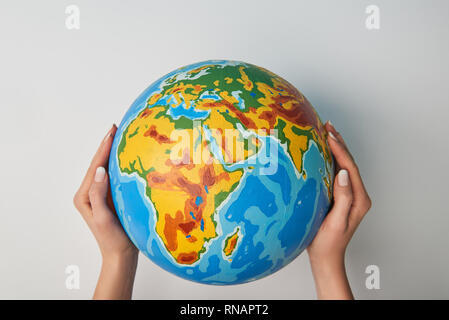 cropped view of woman holding globe on white background - Stock Photo