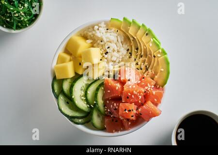 Raw Organic Poke Bowl with with rice, avocado, salmon, mango, cucumbers, chuka salad and soy sauce close-up on white table background. Top view - Stock Photo