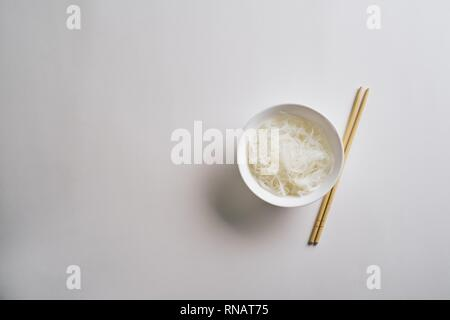 Rice noodles in a plate. Boiled rice noodles in a plate on a white background - Stock Photo