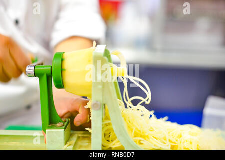 Vegetable Blade Spiralizer, Spiral vegetable slicer with potato spaghetti on table - Stock Photo
