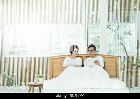 Elderly couple, resting on the bed - Stock Photo