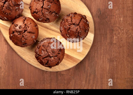 Chocolate muffins, shot from the top on a dark rustic wooden background with copy space - Stock Photo
