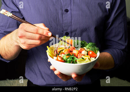 man in a shirt holds poke bowl with salmon, avocado, cucumbers, arugula, broccoli, rice, carrots, cheese and chuha with chopsticks - Stock Photo