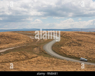 Curving road through tussock country on Ngamatea Station, Inland Mokai Patea, Central North Island, New Zealand - Stock Photo