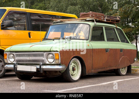 Vintage car with suitcases on the roof. Abandoned auto in the parking lot - Stock Photo