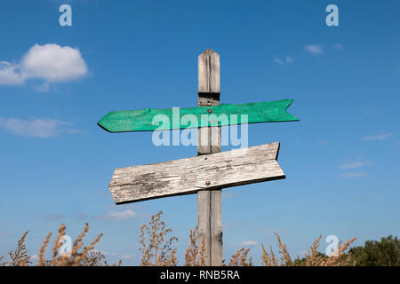 old wooden signpost with two arrows with copy space - Stock Photo