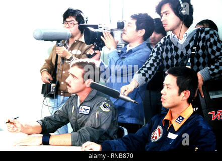 A Japanese national television crew documents the briefing of U.S. Air Force and Japanese Air Self Defense Force pilots during exercise Cope North '80.  A U.S. Air Force F-4E Phantom II aircraft pilot assigned to the 3rd Tactical Fighter Wing is to the left. - Stock Photo