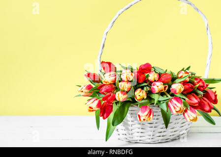 Basket with flowers, bouquet of tulips on yellow background. Women day card or mothers day flower, bunch of colorful spring tulip. - Stock Photo