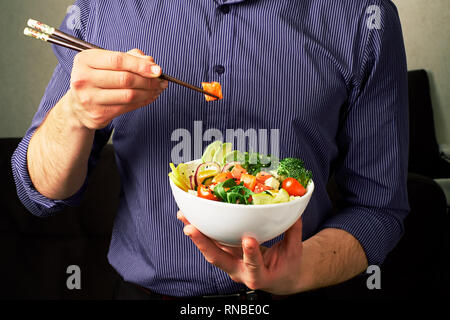man in a shirt holds poke bowl with salmon, avocado, cucumbers, arugula, broccoli, rice, carrots, and chuha with chopsticks - Stock Photo