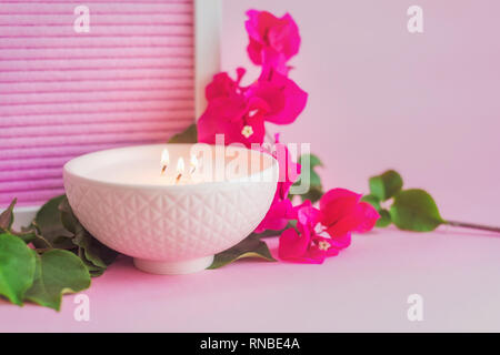 pink ceramic bowl with candle, and pink flower, on a pink background - Stock Photo