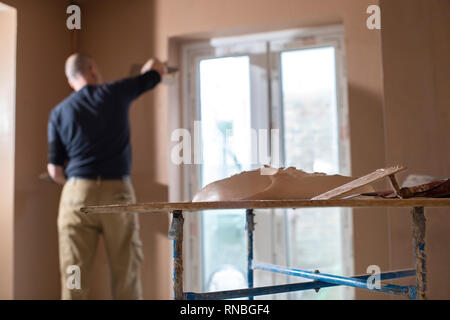 Rear View Of Plasterer Plastering Wall In Room Of House - Stock Photo