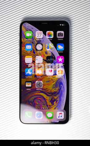 PARIS, FRANCE - SEP 27, 2018: new iPhone Xs Max smartphone model by Apple Computers close up with all home apps against stripes white background - Stock Photo