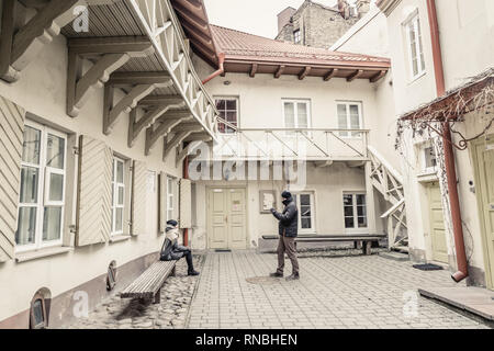 Vilnius, Lithuania - March, 11, 2017:  Tourist making pictures in a small courtyard in the old town Vilnius, Lithuania - Stock Photo