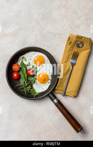 Pan and fried eggs for breakfast with herbs at beige background. Concept of breakfast dish. View from above. - Stock Photo