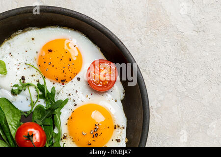 Free space with fried eggs with herbs and cherry tomatoes on pan. Left edge corner, free space - Stock Photo