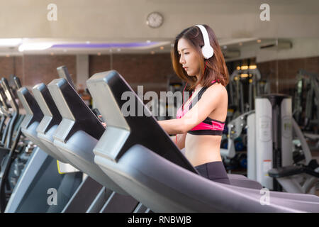 Young girl wearing a pink exercise suit white earphone is walking on the treadmill in the fitness center or gymnasium.