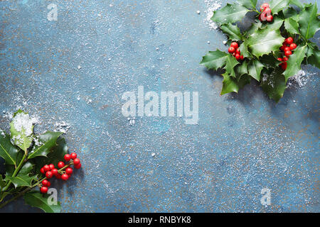 Christmas background with real holly leaves and red berries on a blue stone background covered in snow with copy space. - Stock Photo