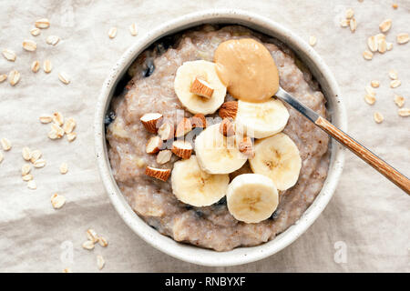 Bowl of oatmeal porridge with banana and peanut butter over linen background. Top view. Healthy vegan breakfast - Stock Photo