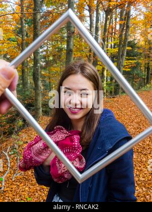 Pretty teen girl is smiling at camera framed by picture flramed hand held before camera giggle giggling - Stock Photo