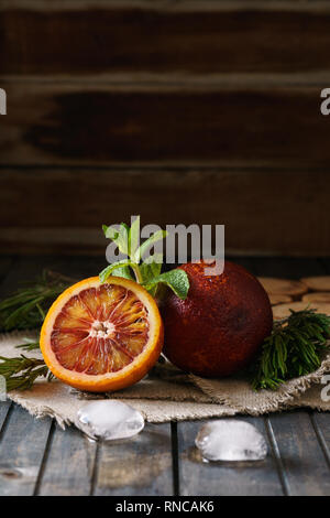 Sliced and whole ripe juicy blood oranges and ice on wooden background. - Stock Photo