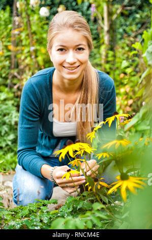 Junge Frau mit langen, blonden Haaren hockt vor einem Strauch Sonnenhueten / Rudbeckia im Garten. [(c) Dirk A. Friedrich - Stock Photo