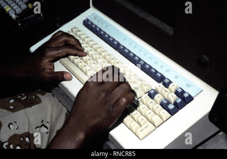 A radioman of the Joint Communications Support Element checks a computer terminal for the day's incoming messages.  He is participating in Exercise SHADOW HAWK '87, a joint Jordan/US Exercise within Exercise BRIGHT STAR '87.  SHADOW HAWK is a combined effort of the US Central Command and the Joint Chiefs of Staff. - Stock Photo