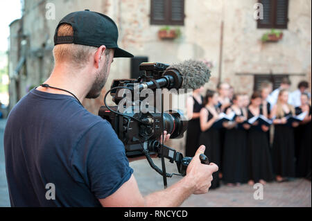 Cameraman captures video and audio whit professional video camera, during a choir live concert - Stock Photo