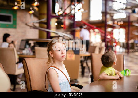 5841166d Food court in Sun City mall · Blonde girl in white and blue dress having  lunch in the restaurant. RUSSIA, SOCHI
