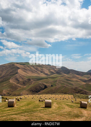 Large round hay bales scattered over a paddock field, beneath brown grass hills, Taihape Napier Road, Inland Patea, Central North Island, New Zealand - Stock Photo