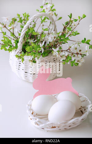 Happy easter. Decor and table setting of the Easter table is a vase with pink tulips and dishes of pink and green color. Selective focus. - Stock Photo