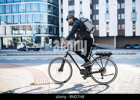 Male courier with bicycle delivering packages in city. Copy space. - Stock Photo