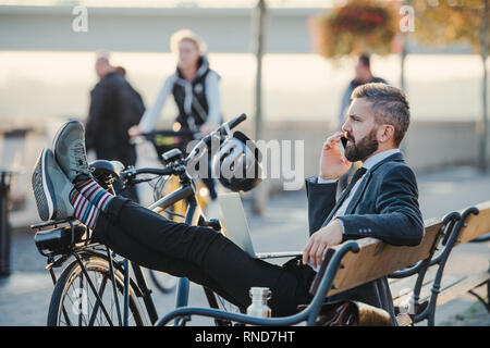 Businessman commuter with bicycle sitting on bench in city, making a phone call. - Stock Photo