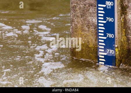 water level pole on a concrete wall in river - Stock Photo