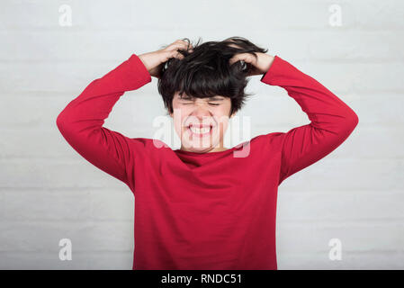 boy scratching his hair for head lice against brick background - Stock Photo
