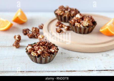 Chocolate popcorn in rustic baking molds on a wooden table - Stock Photo