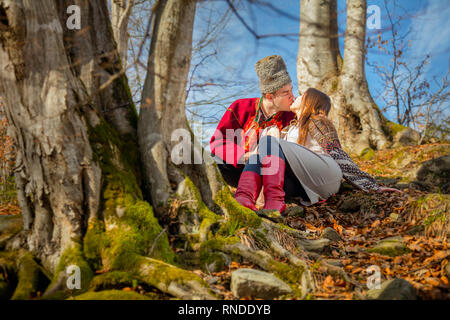 Young happy couple, kisses and love,  local traditional clothes and sunny day in natural forest, european man and woman - Stock Photo