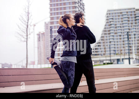 Male coach helping young woman exercising at outdoors in urban environment - Stock Photo