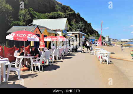 Sandown, Isle of Wight, UK. June 21, 2018.  holidaymakers and schoolchildren on the promenade walk to Sandown from Shanklin with alfresco refreshments - Stock Photo