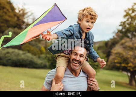 Little boy holding a kite sitting on his father's shoulders at the park. Happy father and son flying kite outdoors.