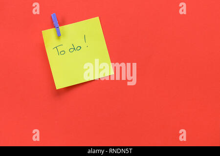 Yellow sticky note with text 'To do'  isolated on a red background and copy space - Stock Photo