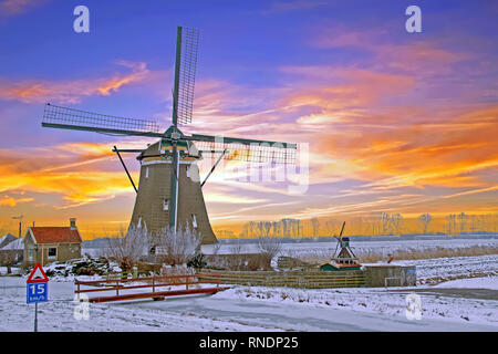 Historical windmill in the countryside from the Netherlands in winter at sunset - Stock Photo