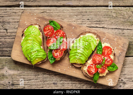 healthy avocado toasts with avocado, cherry tomatoes, basil and sesame seeds on wooden cutting board. top view - Stock Photo