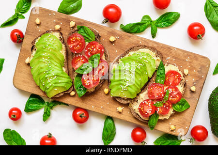 Avocado toast. Healthy toasts with avocado, cherry tomatoes, basil and sesame seeds on wooden cutting board. top view - Stock Photo