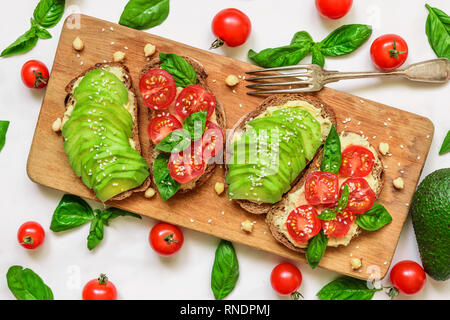 sandwiches with avocado, tomatoes, basil, hummus and sesame seeds on rustic cutting board over white marble table. Healthy breakfast. top view - Stock Photo