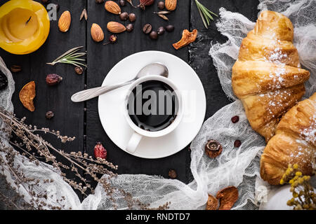 Cup of black coffee and croissants on black background, top view. Flat lay of espresso and cornetto rolls on dark rustic table