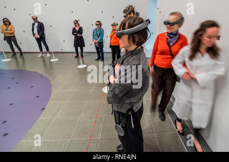 London, UK. 18th Feb, 2019. Visitors are guided by technicians in white coats and watch the installation through goggles - Marina Abramović, The Life at the Serpentine Gallery, a perfomance in Mixed Reality (a wearable augmented experience). The piece, lasting 19 minutes, builds on the artist's long-standing fascination with the notion of material absence. The use of Mixed Reality allows Abramović to explore how to use her own body as subject and object, mapping new territory at the intersection of technology and performance. Credit: Guy Bell/Alamy Live News - Stock Photo