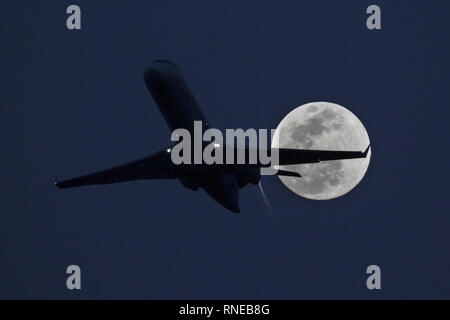 Phoenix, Arizona, USA. 18th Feb, 2019. February 18, 2018 - Phoenix, Arizona, USA - An American Airlines jet takes off from Phoenix Sky Harbor International Airpor as a super moon rises in the distance. Credit: KC Alfred/ZUMA Wire/Alamy Live News - Stock Photo