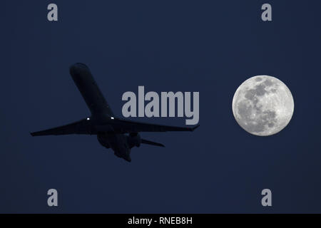 Phoenix, Arizona, USA. 18th Feb, 2019. February 18, 2018 - Phoenix, Arizona, USA - An American Eagle jet takes off from Phoenix Sky Harbor International Airpor as a super moon rises in the distance. Credit: KC Alfred/ZUMA Wire/Alamy Live News - Stock Photo