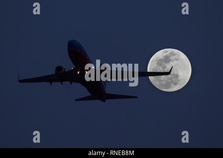 Phoenix, Arizona, USA. 18th Feb, 2019. February 18, 2018 - Phoenix, Arizona, USA - A Southwest Airlines 737 takes off from Phoenix Sky Harbor International Airpor as a super moon rises in the distance. Credit: KC Alfred/ZUMA Wire/Alamy Live News - Stock Photo