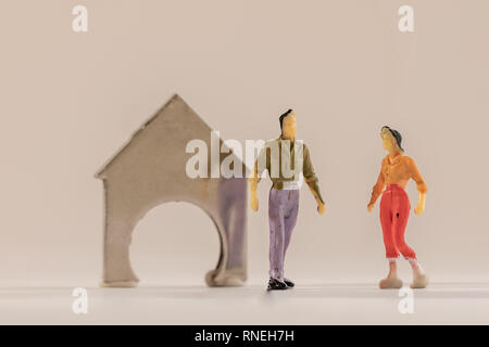 Miniature woman and man figure standing next to house made of coin holder with no coins. Shallow depth of field background. Family budget, mortgage an - Stock Photo
